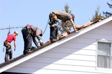 Roof Installation in North Tustin CA. Three roofers laying new shingle on a roof in North Tustin.